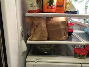 Simple juicing hacks store pre-made green juice in brown lunch bags in fridge