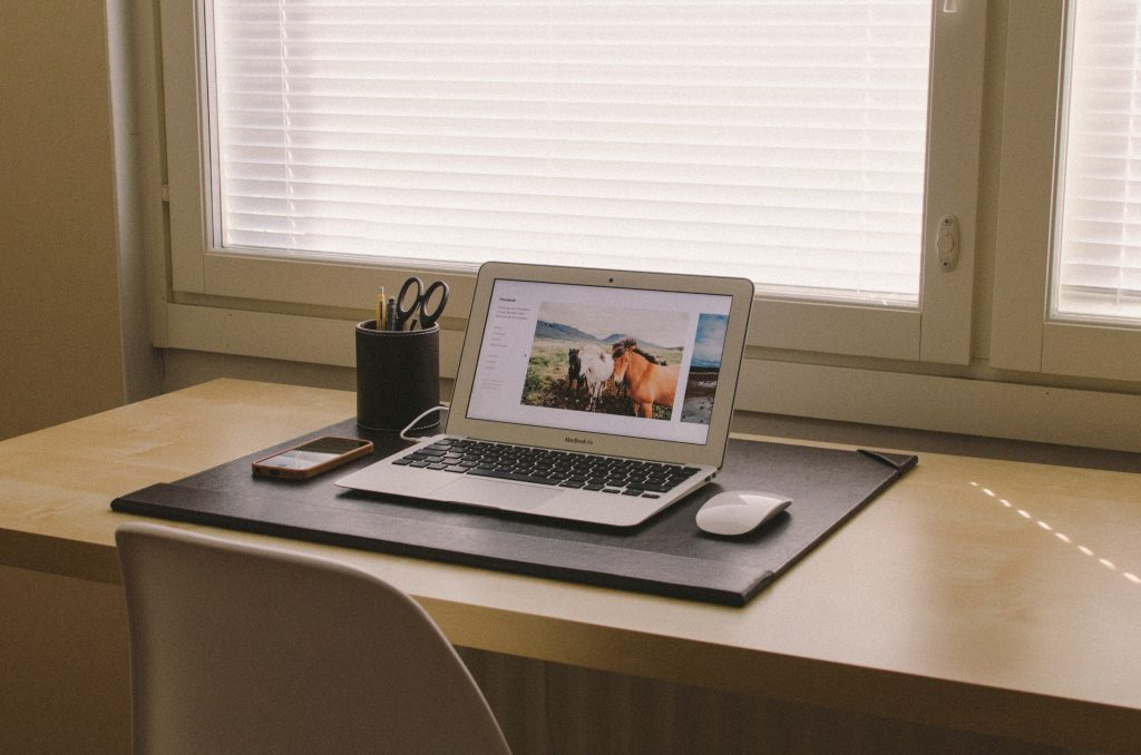 organizing tips an organized desk with Mac laptop, wireless mouse on desk pad