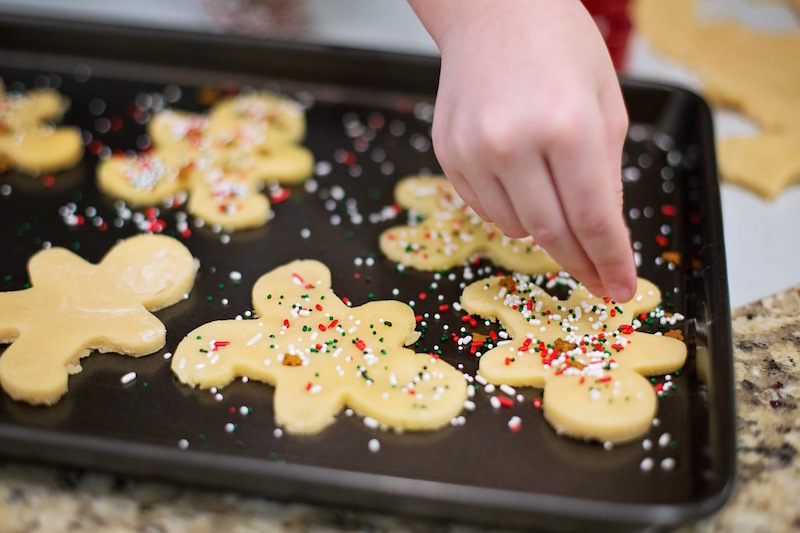 How to organize your home for the holidays. Child decorating sprinkles on homemade Christmas cookies